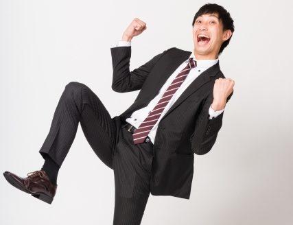ガッツポーズをしているスーツ姿の男性